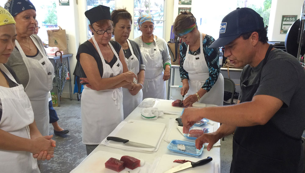 People learning how to slice fresh ahi