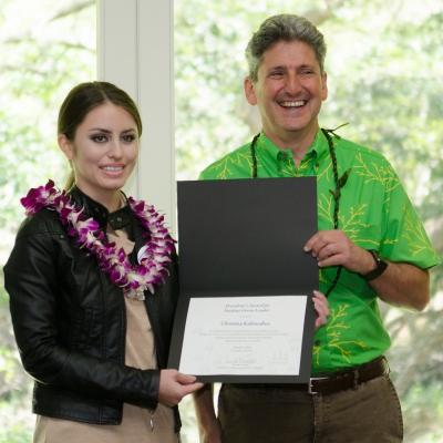 Hawaiian Electric Companies vice president Scott Seu, left, and UH President David Lassner, right, present Christina Kaleiwahea with a Green Student Leader Award.